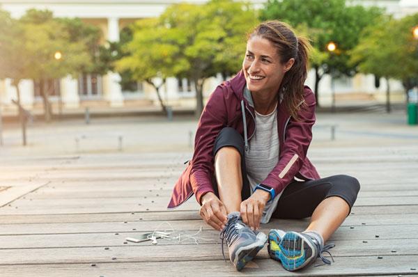 woman tying her shoe getting ready to run