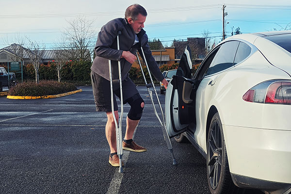 crippled man struggling to get into his car