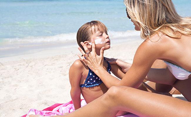 woman applying sun screen to her child